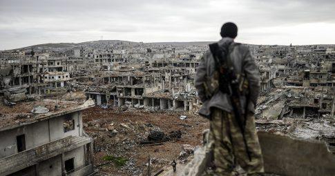 Atirador curdo sob escombros em Ain al-Arab em 2015 -  Credit Bulent Kilic/Agence France-Presse — Getty Images